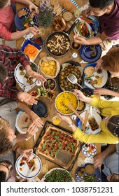 High angle of people sharing food at a table with pizza, hummus and salads