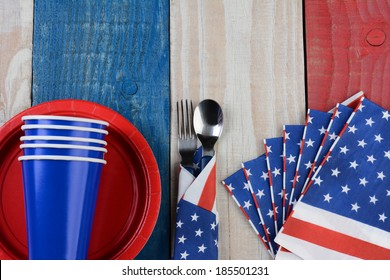High angle photo of a Fourth of July picnic table setting. The red white and blue items are on a wood table painted for the holiday.