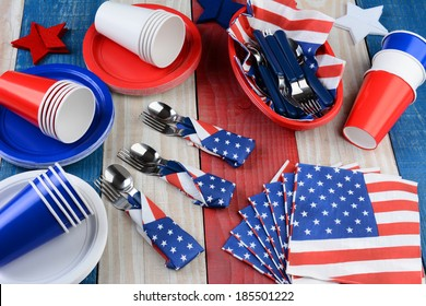HIgh angle photo of a picnic table setting for a Fourth of July party. Plates, cups, napkins, and other items in patriotic red, white and blue. Horizontal format.