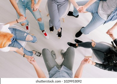 High angle photo of teens and therapist holding hands during session in a rehab center