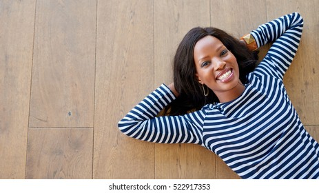 High angle portrait of an attractive young woman smiling while lying with her hands behind her head on a wooden floor at home