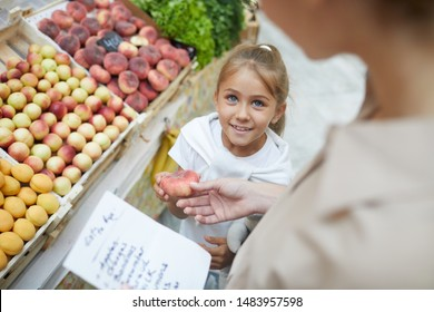 High angle portrait of cute little girl smiling at mom while shopping at farmers market together, copy space