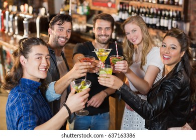High angle portrait of happy friends holding drinks while standing together in bar
