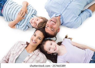 High angle portrait of happy parents and children lying on white background