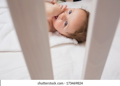 High angle portrait of lovely baby with finger in mouth lying on crib