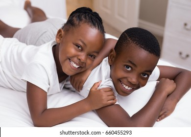 High angle portrait of smiling siblings lying on bed at home