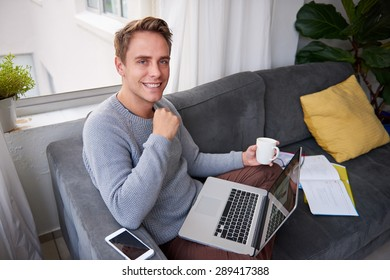 High angle portrait of a smiling young man sitting on his couch at home with his laptop and a cup of coffee
