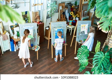 High angle portrait of three children painting on easels during art class in cozy studio decorated with plants, copy space