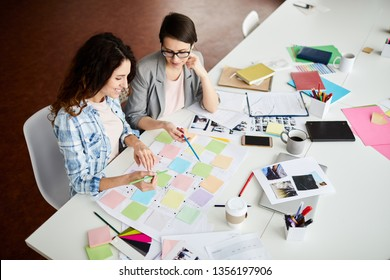 High angle portrait of two contemporary women planning project placing colorful stickers on roadmap, copy space