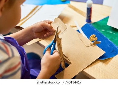 High angle portrait of unrecognizable little boy cutting paper in arts and crafts class of pre-school making handmade gift