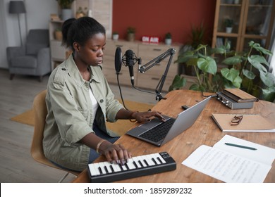 High angle portrait of young African-American woman composing music in home recording studio, copy space