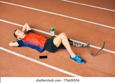 High angle portrait of young amputee athlete relaxing with eyes closed  lying on running track in modern stadium, copy space