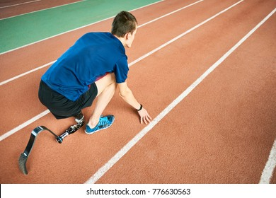 High angle portrait of young amputee athlete on start position on running track in modern indoor stadium, copy space