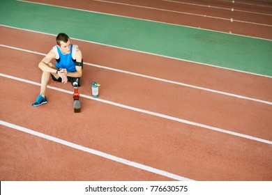 High angle portrait of young amputee athlete sitting on running track taking break from practice to relax, copy space