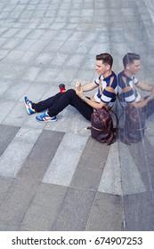 High angle of relaxed boy having break outdoors. Trendy boy listen music, enjoying city panorama