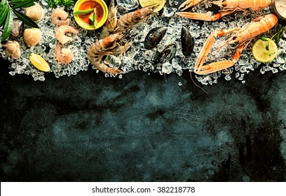 High Angle Seafood Cuisine Background Image with Fresh Shellfish - Shrimp, Langostino, Mussels and Clams - and Ingredients Chilling on Ice on Dark Background with Copy Space