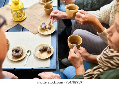 High angle of several senior people drinking tea with chocolate doughnuts meeting in outdoor cafe round table