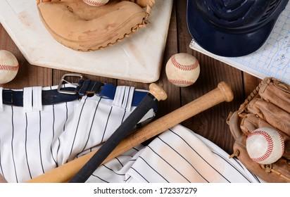 High angle shot of baseball gear on a rustic wood surface. Items include, Home Plate, helmet, baseball, ball, glove, catchers mitt, score book, pants, belt and bats.