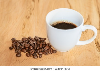 High angle shot of a bunch of coffee beans by a coffee cup