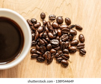 High angle shot of a bunch of coffee beans and a half full coffee cup