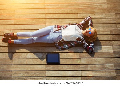 High angle shot of carefree young woman in summer glasses lying on the wooden jetty in the sun,young freelancer woman resting after work with digital tablet outdoors, enjoy her holiday or break, flare