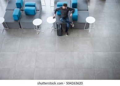 High angle shot of casual man sitting in a lobby with his luggage.