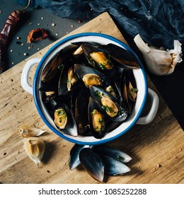 high angle shot of a ceramic bowl with moules mariniere, a french recipe of mussels, on a rustic wooden table