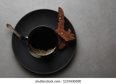 High angle shot of Chocolate Biscotti and Coffee cup and saucer on a slate gray  table.