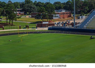 High angle shot of a football field with a man mowing on a reel mower