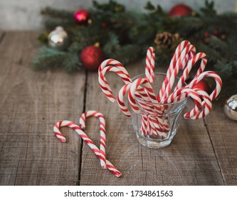 High angle shot of a glass of candy canes against Christmas backdrop.