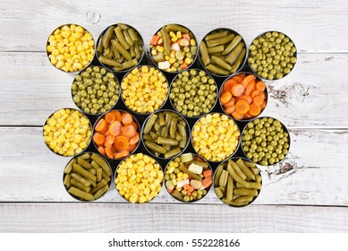 High angle shot of a group of canned vegetables on a rustic white wood table. Several varieties of opened cans including, corn, green beans, peas, carrots and mixed veggies.