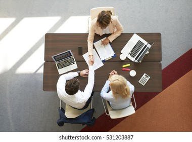High angle shot of an investment advisor shaking hands with professional businessman while sitting on meeting.