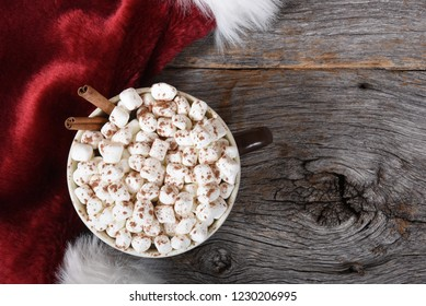 High angle shot of a large mug of hot cocoa with marshmallows on a rustic wood table next to a Santa Hat.