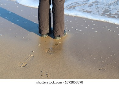 A high angle shot of a male's shoeprint on the beach sand