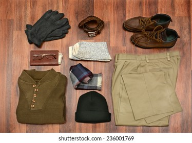 High angle shot of men's winter clothes laid out on a dark wood floor. Items include, Sweater, Scarf, Gloves, wool Socks, Pants, Boots, belt, Knit Cap, Wallet, and Glasses. Horizontal Format.