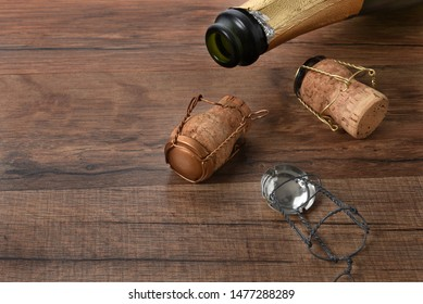 High angle shot of an ope bottle of champagne with corks on a wood table with copy space.