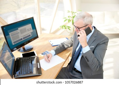 High angle shot of senior financial consultant businessman wearing suit while sitting at office desk in front of laptop and making call.