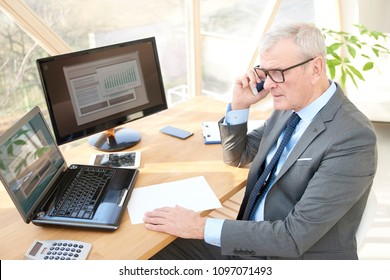 High angle shot of a senior sales man sitting at office desk in front of laptop and talking with somebody in his mobile phone.