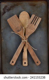 High angle shot of three wooden kitchen utensils crossed and tied with a piece of twine on a used metal baking sheet. Vertical Format.