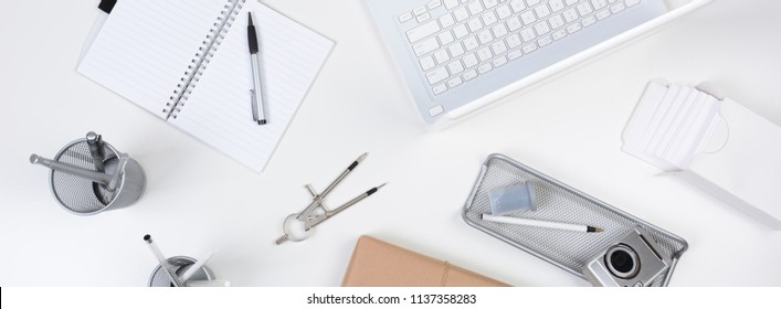 High angle shot of a white desk with primarily white and silver office objects. Items include, laptop, computer, pad, pens, camera. Banner Format.