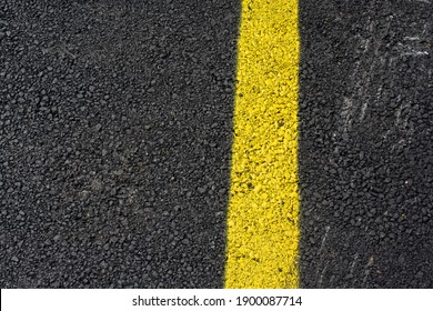 A high angle shot of a yellow line painted on the asphalt