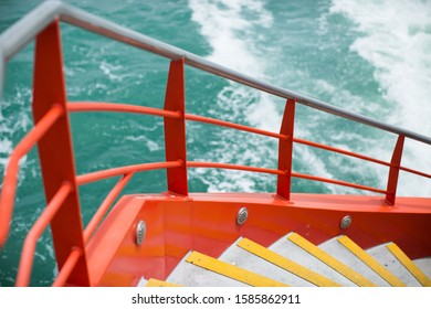 A high angle shot of yellow stairs with red railings near the sea