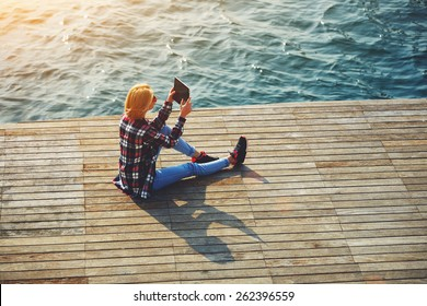 High angle shot of young tourist woman taking a photo of a beautiful view with her camera tablet, cute hipster girl relaxing at her sunny holiday photographing outdoors, young woman on sea pier, flare