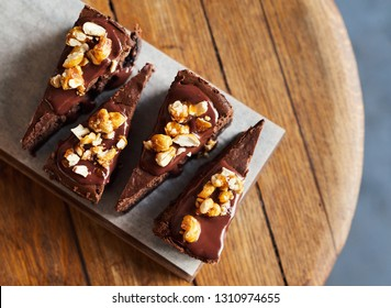 High angle of slices of delicious looking freshly made nutty chocolate pie sitting on a serving board on a wooden bakery table