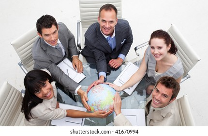 High angle of smiling business team holding the world. Worldwide business