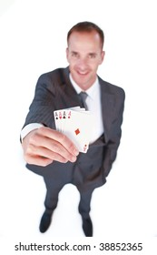 High angle of a smiling businessman holding four aces poker cards