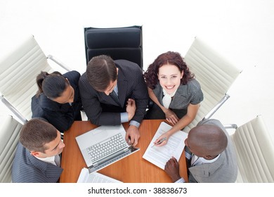 High angle of smiling businesswoman working with her team with a laptop
