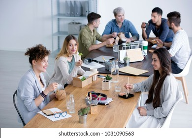 High angle of smiling women eating lunch in corporation canteen during break