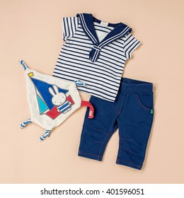 High Angle Still Life of Baby Clothing Laid Out on Beige Background - Nautical Themed Baby Outfit of Blue Jeans and Striped Top Arranged Neatly on Studio Surface