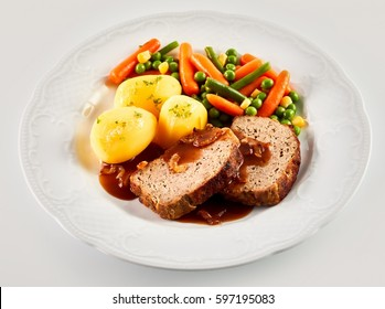 High Angle Still Life of Hearty Dinner Meal - Slices of Meatloaf with Brown Gravy, Roasted Potatoes, and Mixed Vegetables Served in White Dish on White Background
